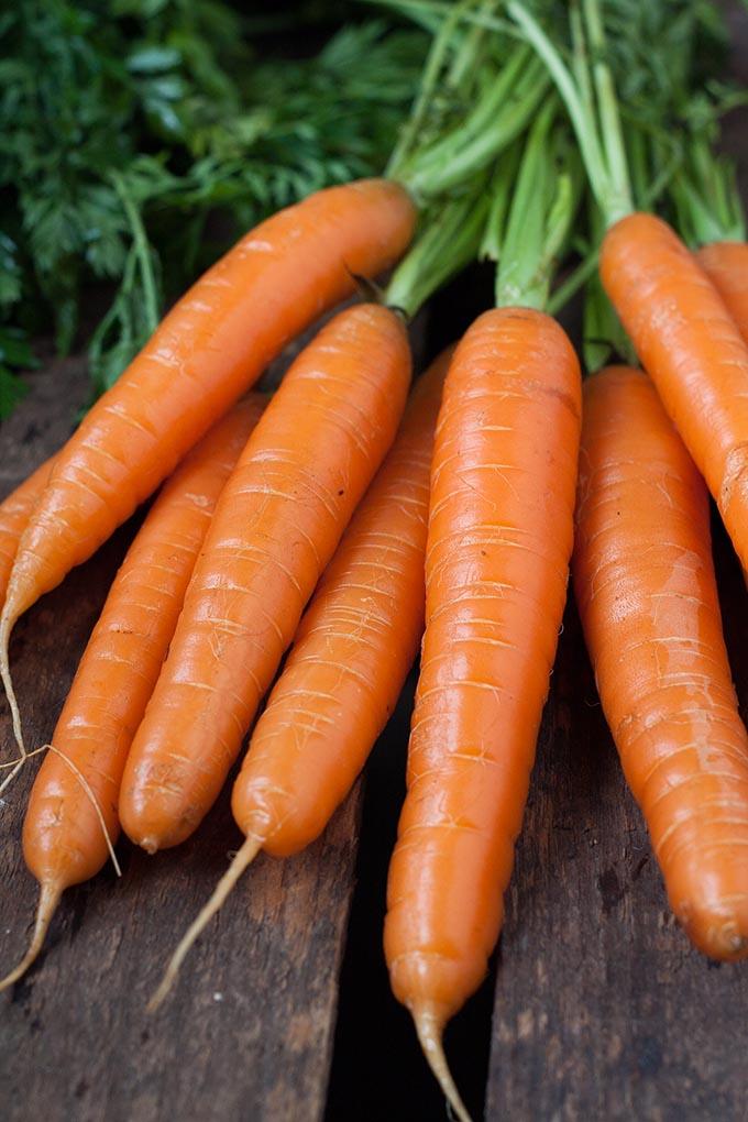 Karotten mit Karottengrün auf Holz - Kochkarussell.com