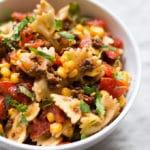 Einfacher Taco Nudelsalat mit würzigem Hackfleisch, Tomaten, Nudeln, Mais, Koriander und Taco Sauce. Super schnell gemacht und SO gut - Kochkarussell.com