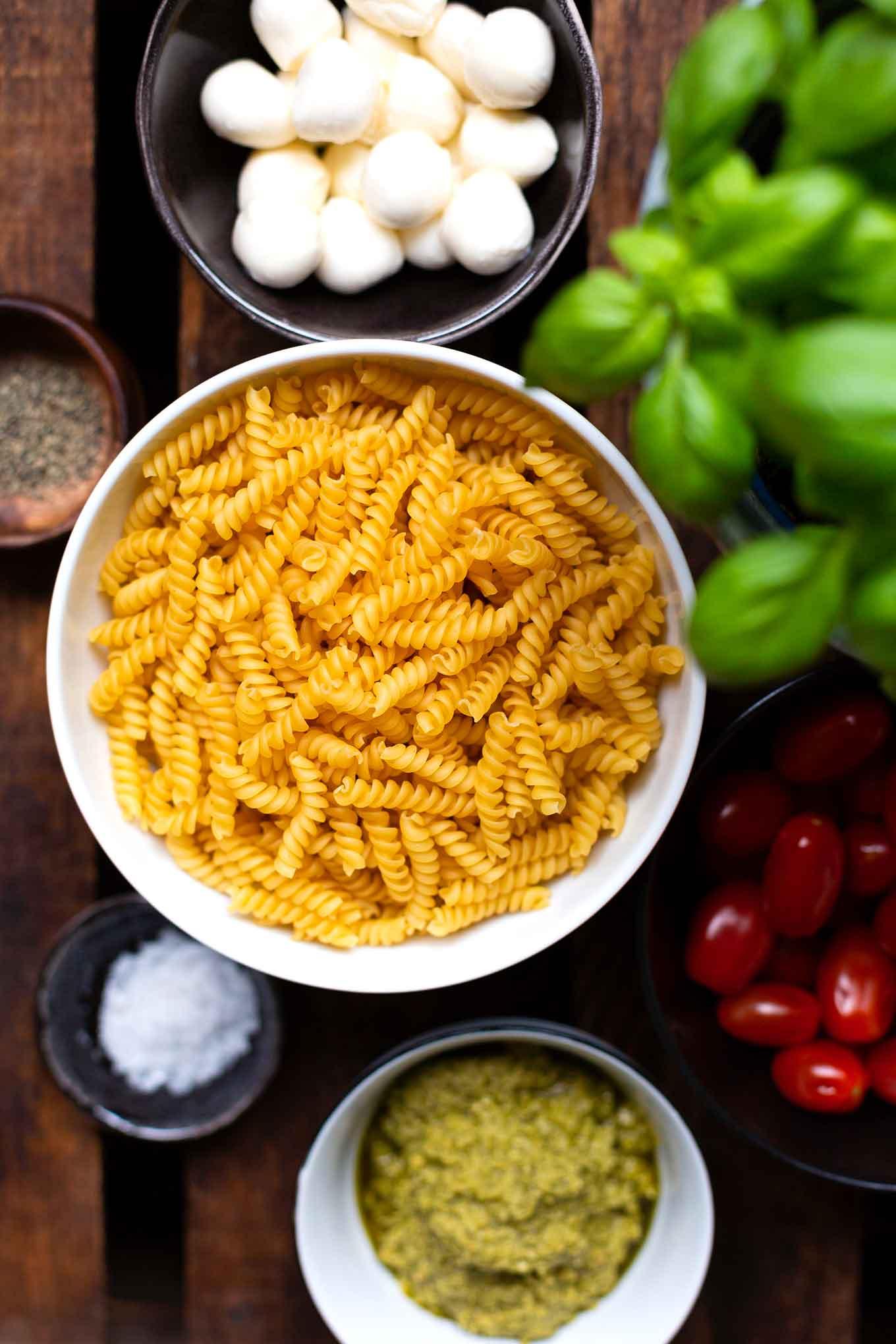 20-Minuten Caprese-Nudelsalat. Super einfach und SO lecker. Für dieses schnelle Rezept braucht ihr nur eine Handvoll Zutaten. Unbedingt probieren - Kochkarussell Foodblog #nudelsalat #pesto #caprese #kochkarussell